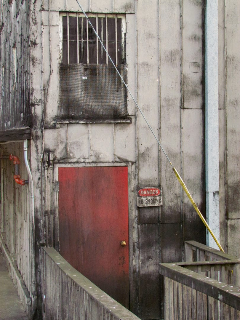 A red door of a worn down-looking building