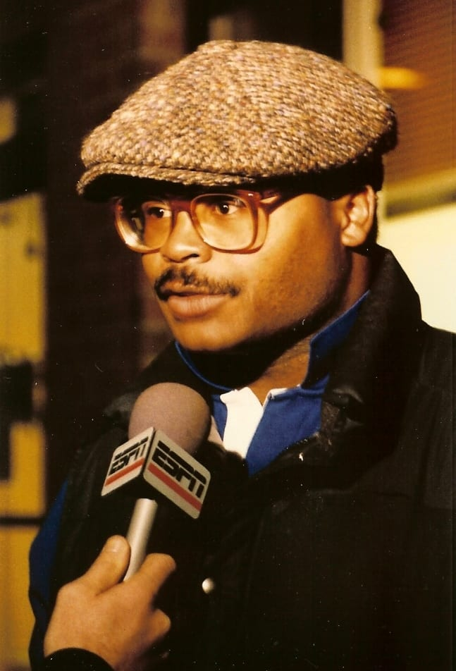 A man with a cap and glasses being interviewed