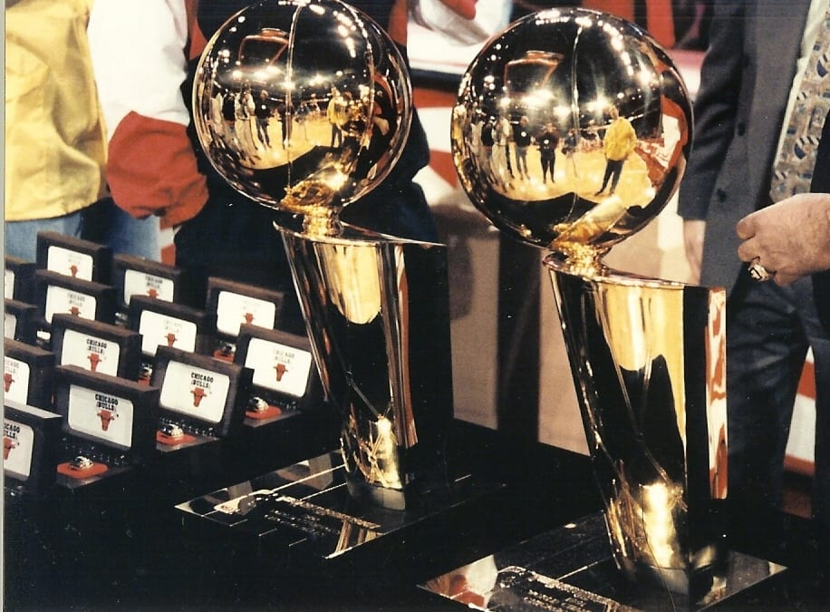 Two basketball trophies next to ring boxes