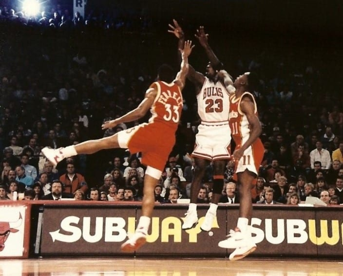 Two players attempt to block MJ