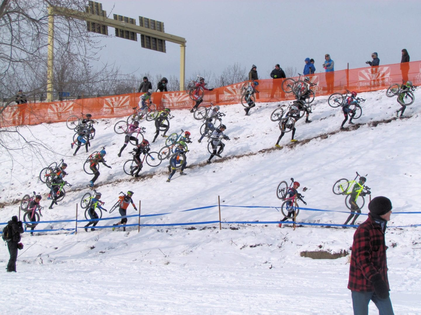 Cyclists carry their bikes over snow