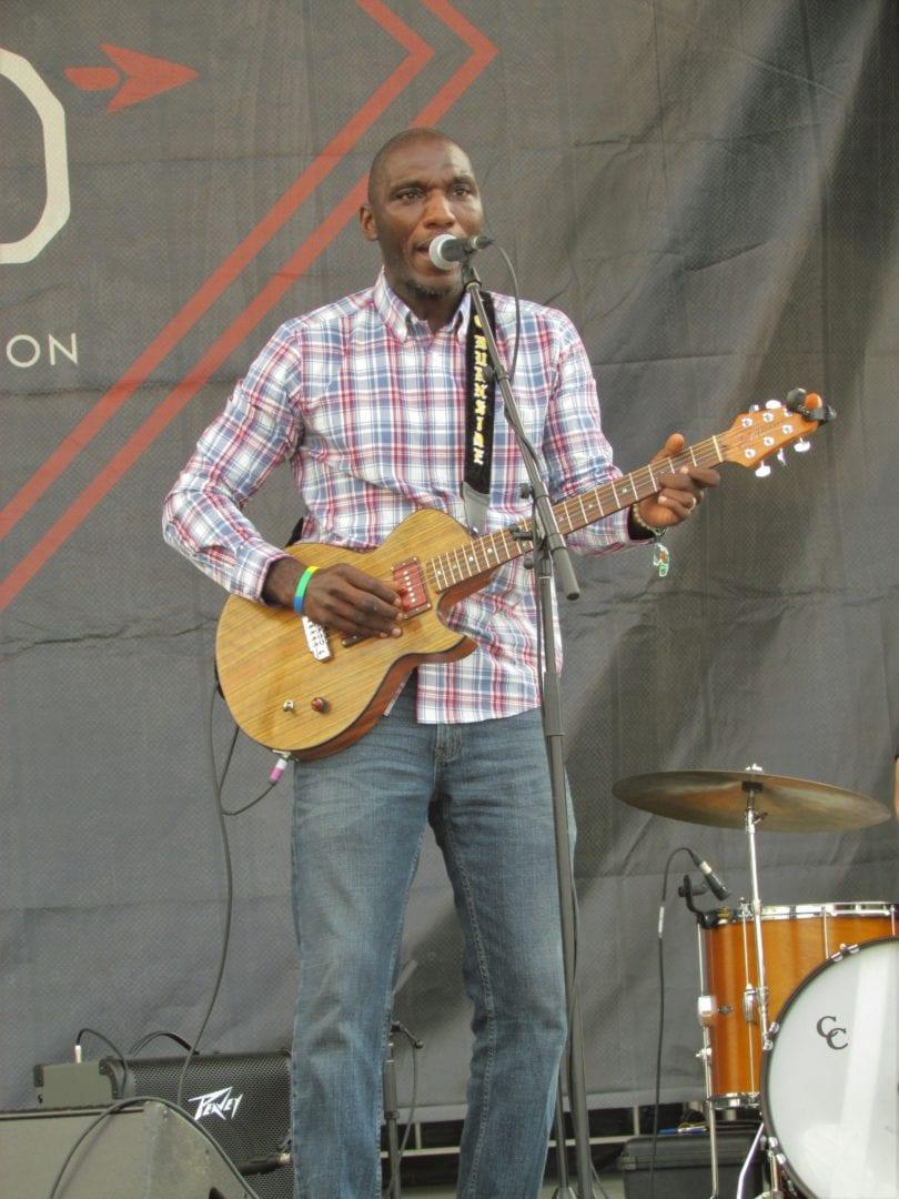 Cedric Burnside strumming his guitar