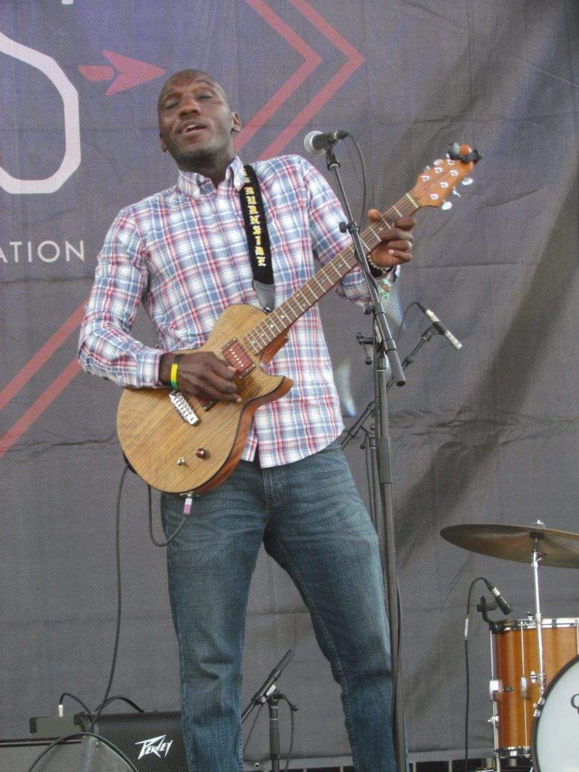 Cedric Burnside playing a guitar on stage