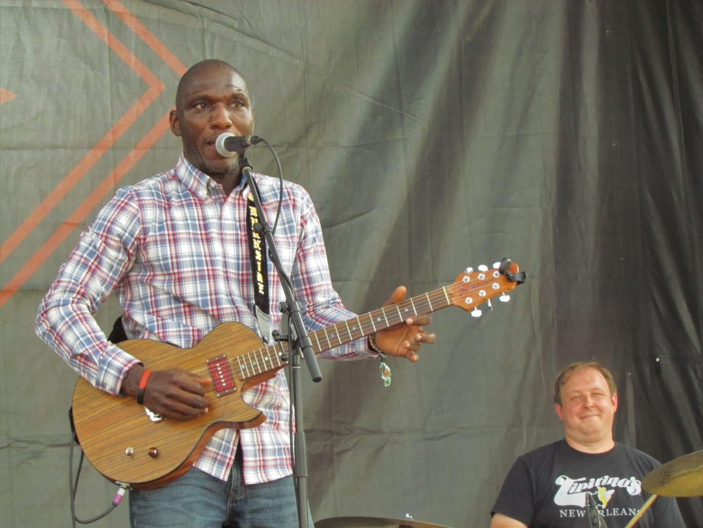 Cedric Burnside playing a guitar while singing