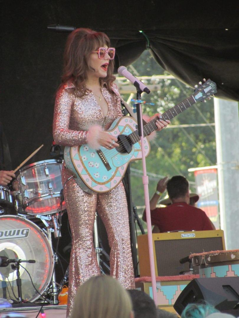 Jenny Lewis strumming her guitar
