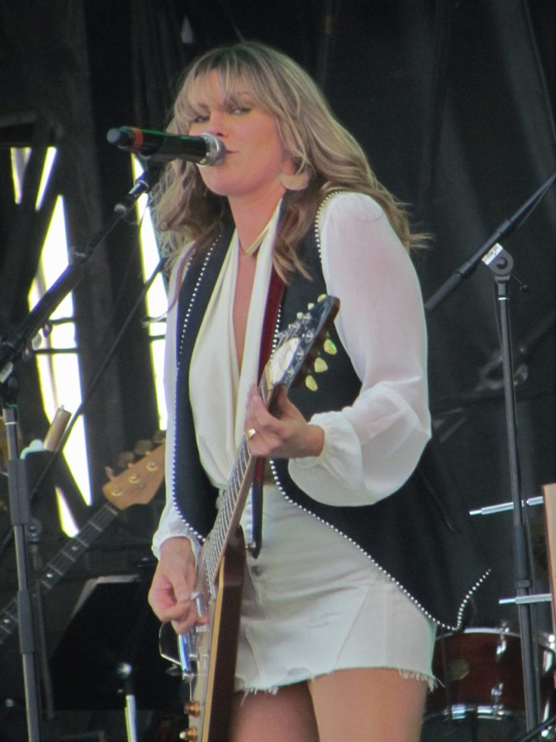 Grace Potter playing her guitar while singing