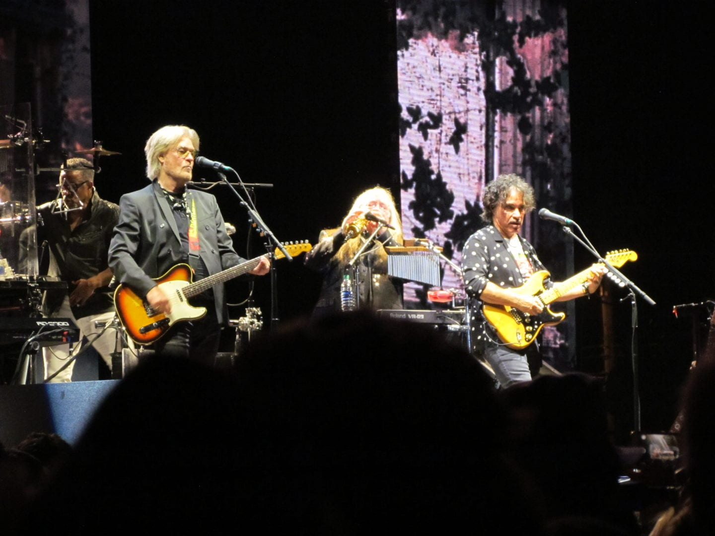 Hall Oates playing his guitar with his band member