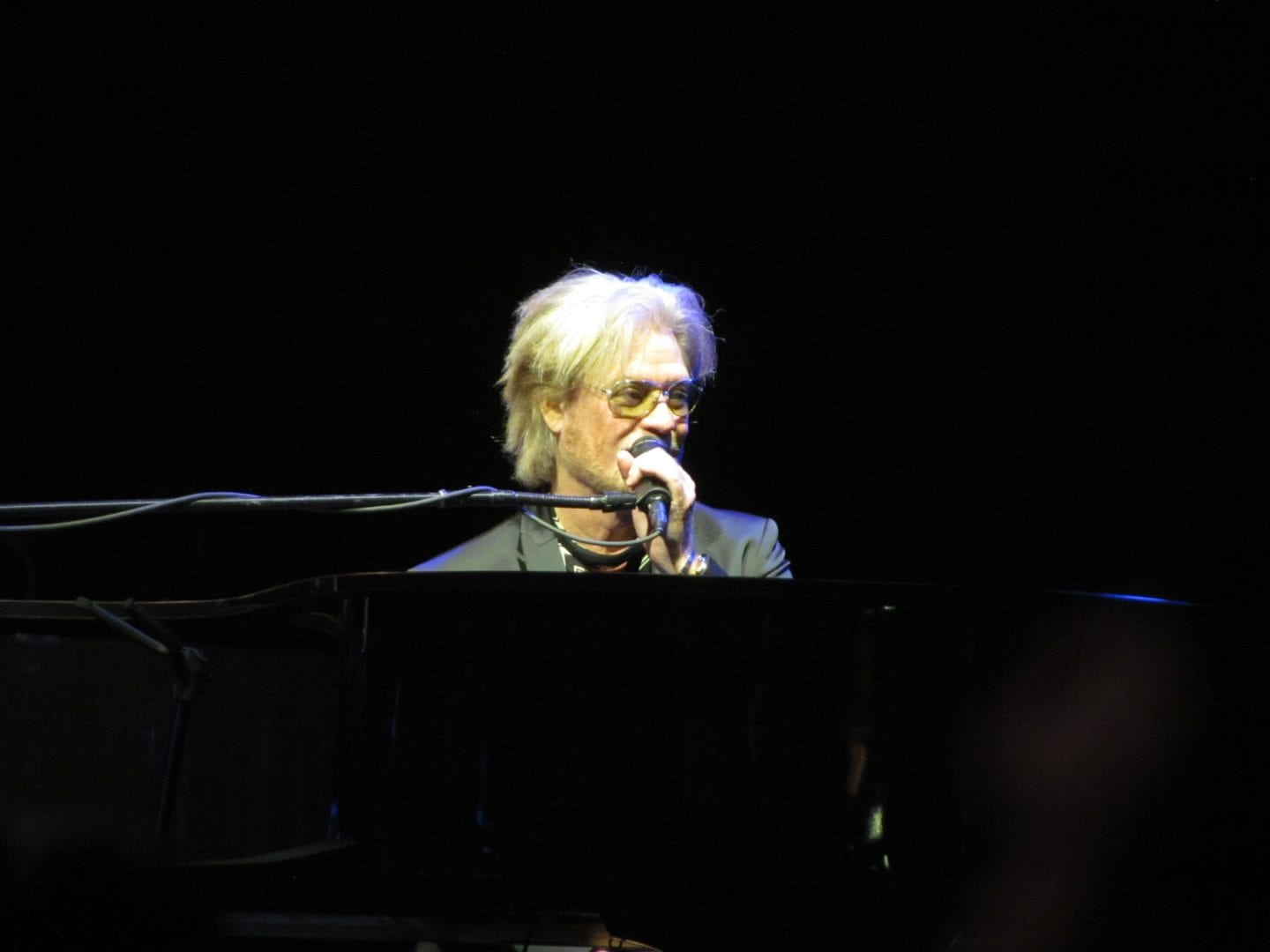 Daryl Hall singing a song while playing the keyboard