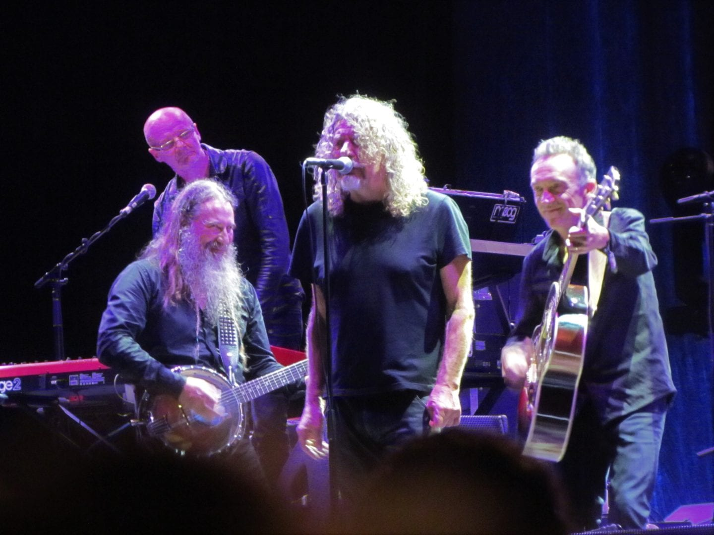 Robert Plant singing on stage with his band mates