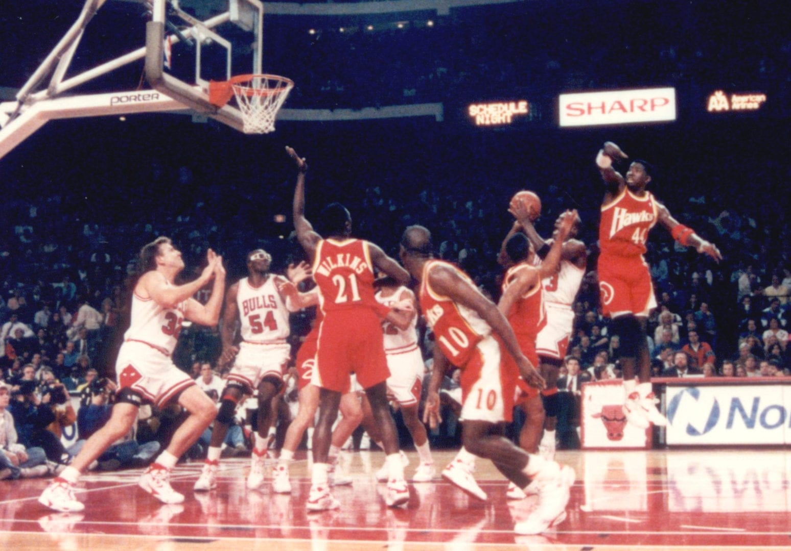 MJ doing a jump shot over a crowd of players