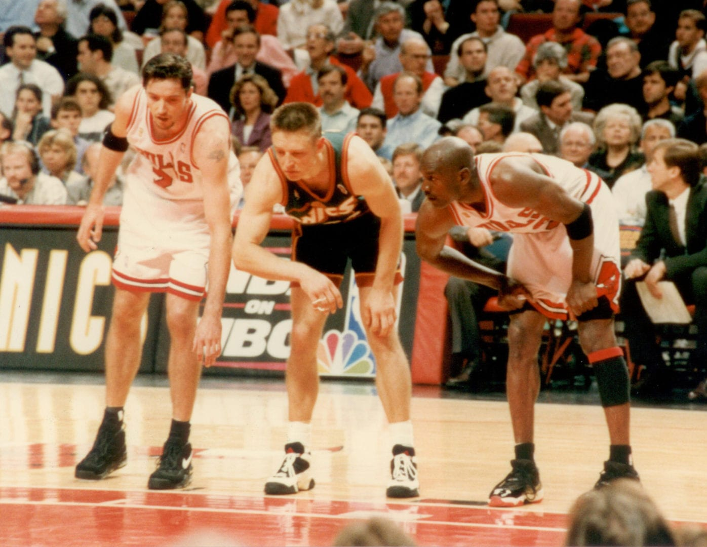 Three players lookin at the center of the court