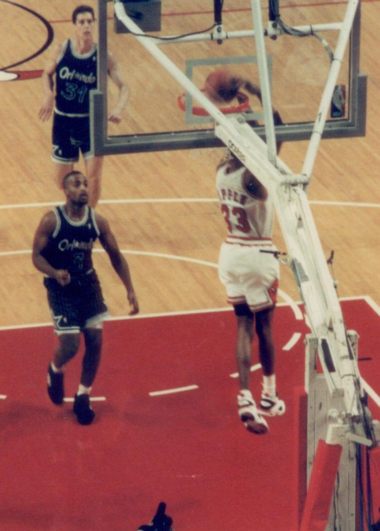 Scottie Pippen doing a reverse slam dunk