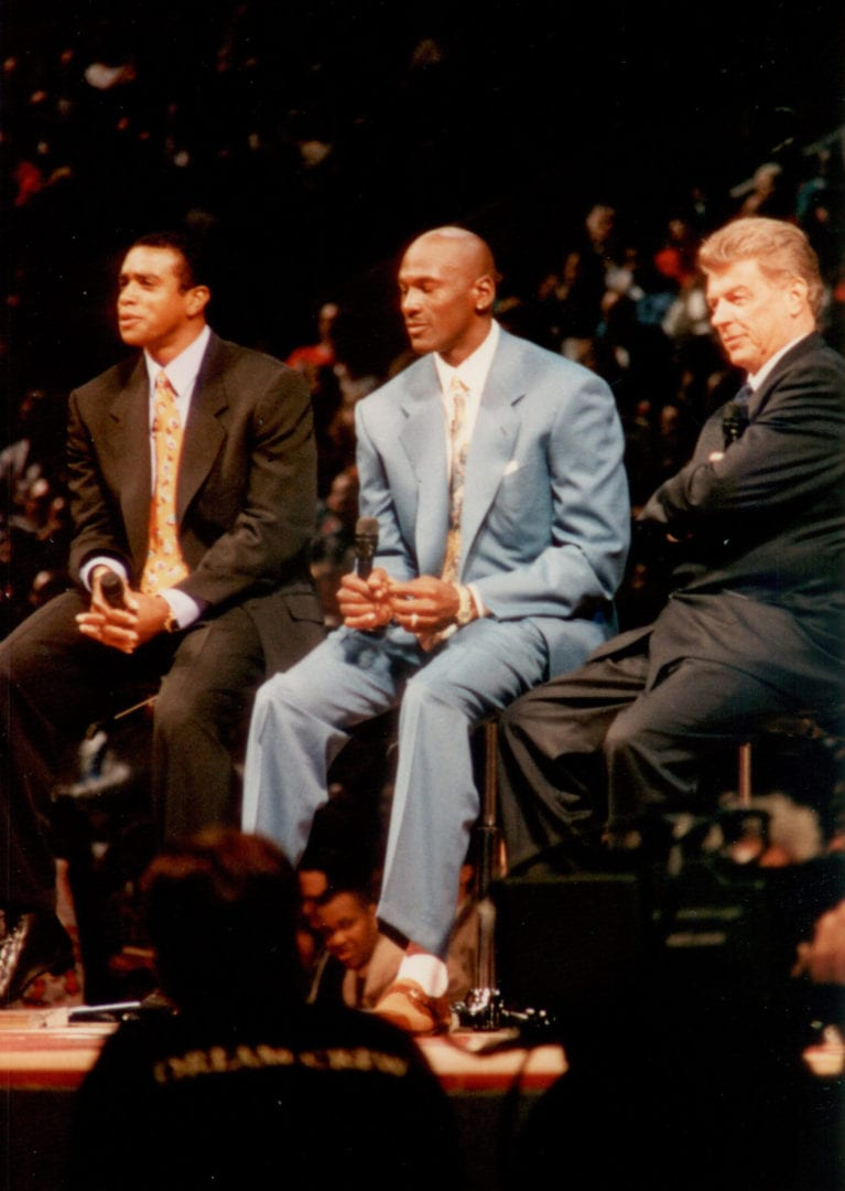 MJ sitting ona chair with other men
