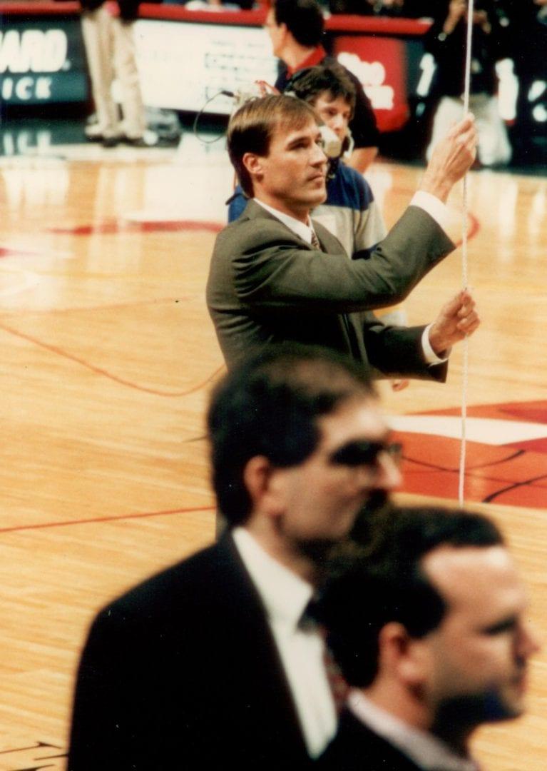 John Paxson holding up an NBA banner